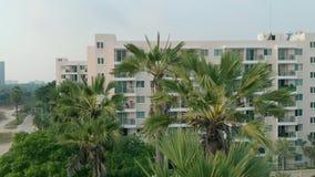 Vue aérienne de village tropical, ville Tir de première vue Paumes environnantes de piscines et jardin vert dans le beau tropical clips vidéos