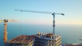 Vue aérienne de ville Construction d'un gratte-ciel ayant beaucoup d'étages sur l'océan par deux grues Ralentissez même le voyage banque de vidéos