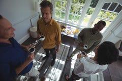Vue aérienne des amis agissant l'un sur l'autre tout en ayant le café Photos libres de droits