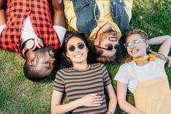 vue aérienne des amis multi-ethniques heureux se reposant sur le vert photo stock