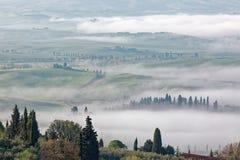 Vue aérienne des fermes de sommet et des arbres de cyprès en Toscane un matin brumeux de ressort | Photos stock