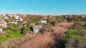 Vue aérienne des maisons de campagne sur la colline sur le rivage de l'étang pendant le matin