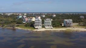 Vue aérienne des maisons de fantaisie, volant au-dessus de la ville et de la plage 4K banque de vidéos
