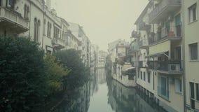 Vue aérienne des maisons résidentielles le long du canal étroit en brouillard Padoue, Italie banque de vidéos