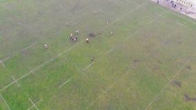 Vue aérienne des personnes jouant un jeu de rugby sur un champ vert en Ukraine Jour brumeux sans soleil banque de vidéos