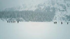 Vue aérienne des personnes méconnaissables trimardant sur le lac neigeux Morskie Oko, Pologne du sud Photographie stock
