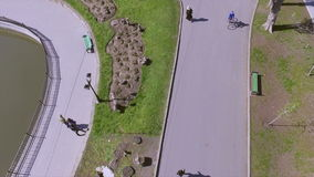 Vue aérienne des personnes marchant en parc une journée de printemps ensoleillée banque de vidéos