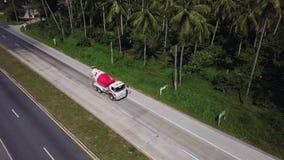 Vue aérienne du camion de mélange de ciment conduisant sur la route parmi la plantation de palmier Vol cinématographique de tir d clips vidéos