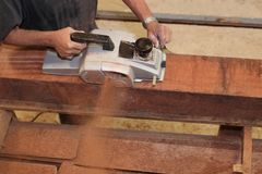 Vue aérienne du charpentier supérieur à l'aide de la planeuse électrique sur un morceau de bois dans l'atelier de menuiserie Foye Photos libres de droits