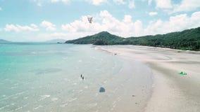 Vue aérienne du kiter un grand cerf-volant s'exerçant blanc sur le bord de la mer Kitesurf extrême de sports dans l'océan bleu tr banque de vidéos