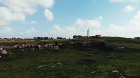 Vue aérienne du phare blanc dans des paphos de la Chypre avec des vagues de ville antique et d'herbe verte et de mer banque de vidéos