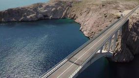 Vue aérienne du pont de l'île du PAG, de la Croatie, des routes et de la falaise croate de côte donnant sur la mer banque de vidéos