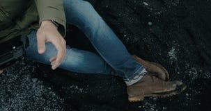 Vue aérienne en gros plan des pieds masculins dans les bottes sur la plage volcanique noire en Islande Hélicoptère contagieux de  clips vidéos