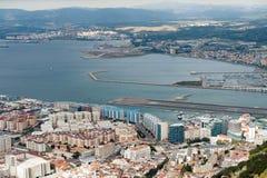 Vue aérienne sur la piste de ville et d'aéroport du Gibraltar et de la ville espagnole de Linea de La sur un fond Images stock