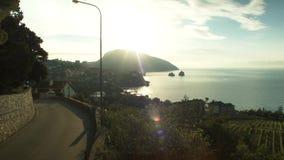 Vue aérienne sur la route par la mer et le ciel dramatique avec le coucher du soleil, fond isolé de roche projectile Coucher du s banque de vidéos