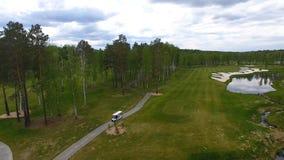 Vue aérienne sur le chariot de golf sur le terrain de golf pendant l'après-midi avec l'espace de copie Club de golf d'élite Photos stock