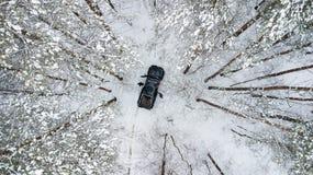 Vue aérienne sur SUV 6x6 qui monte par la route d'hiver dans la forêt couverte de neige Images stock
