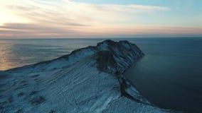 Vue aérienne sur un cap rocheux couvert par la neige dans l'eau de mer foncée contre le ciel nuageux au lever de soleil projectil clips vidéos
