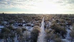 Vue aérienne : Voler au-dessus de la route couverte de neige pendant le coucher du soleil banque de vidéos