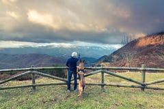 Vue admirative d'homme et de chien en montagnes Image stock