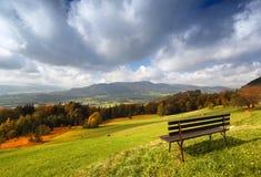 Vue alpine d'automne ensoleillé panoramique avec le banc Photographie stock