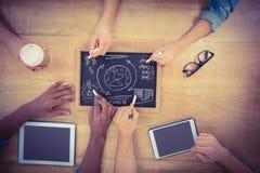 Vue aérienne des mains cultivées écrivant des termes d'affaires sur l'ardoise avec le comprimé numérique émouvant de personne Images stock