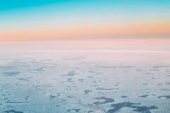 Vue aérienne du vol d'altitude des avions sur la terre couverte de neige Image stock