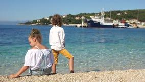 Vue arrière, écoliers garçon bouclé et fille jouant les uns avec les autres sur les rivages du méditerranéen l'adriatique clips vidéos