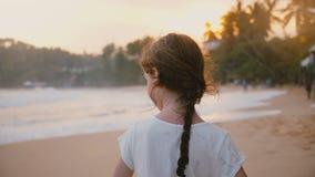 Vue arrière étonnante tirée de la petite position paisible heureuse d'enfant féminin des années 6-8 sur la plage tropicale ensole clips vidéos