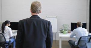 Vue arrière arrière d'homme d'affaires sérieux marchant par le bureau moderne regardant des gens d'affaires de personnel sur des  clips vidéos
