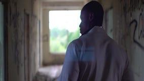 Vue arrière au docteur africain inconnu marchant le long du corridord ruiné de l'hôpital psychiatrique abandonné banque de vidéos