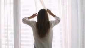Vue arrière arrière au rideau en ouverture heureux riche de jeune femme banque de vidéos
