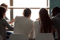 Vue arrière aux personnes multiraciales détendant ensemble partageant le café t Photo libre de droits