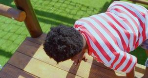Vue arrière d'écolier d'Afro-américain jouant dans le terrain de jeu d'école un jour ensoleillé 4k banque de vidéos