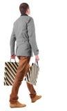 Vue arrière d'homme bel allant avec des sacs à provisions Photographie stock