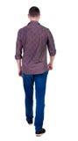 Vue arrière d'homme bel allant dans les jeans et une chemise Photographie stock