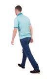 Vue arrière d'homme bel allant dans les jeans et une chemise Image stock