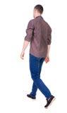 Vue arrière d'homme bel allant dans les jeans et une chemise Photos stock