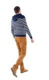 Vue arrière d'homme bel de marche dans les jeans et le chandail rayé Photo libre de droits