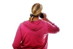 Vue arrière d'un aîné féminin blond à l'aide du téléphone portable Photos libres de droits