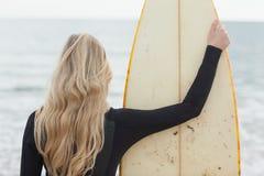 Vue arrière d'un blond dans le vêtement isothermique avec la planche de surf à la plage photo stock