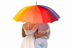Vue arrière d'un couple sous un parapluie coloré image libre de droits
