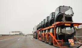Vue arrière d'un grand camion avec la remorque à plat transportant le tracteur Ca Photographie stock