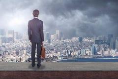 Vue arrière d'un homme d'affaires sur le dessus de toit regardant la ville avec l'espace de copie images stock