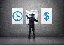 Vue arrière d'un homme d'affaires attachant des affiches et x27 ; le temps est le money& x27 ; sur le mur en béton Photo stock