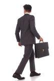 Vue arrière d'un homme d'affaires de marche avec la serviette Image stock