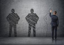 Vue arrière d'un homme d'affaires dessinant le men& foncé x27 ; silhouettes de s sur le mur en béton Photographie stock libre de droits