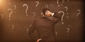Vue arrière d'un homme d'affaires douteux regardant de divers points d'interrogation Image stock