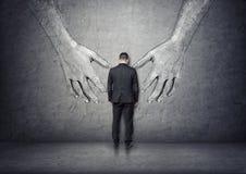 Vue arrière d'un homme d'affaires se tenant entre de grandes mains tirées par la main image libre de droits