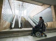Vue arrière d'un homme handicapé sur le fauteuil roulant en escalator de Front Of et d'escalier avec l'espace de copie images stock